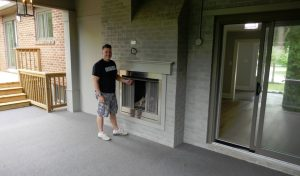 Keith the builder beside outdoor fireplace, backyard patio